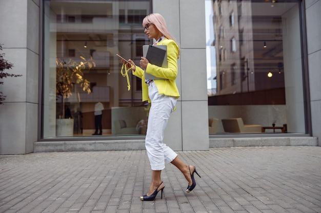 歩きながら携帯電話の画面を見つめているハイヒールの女性