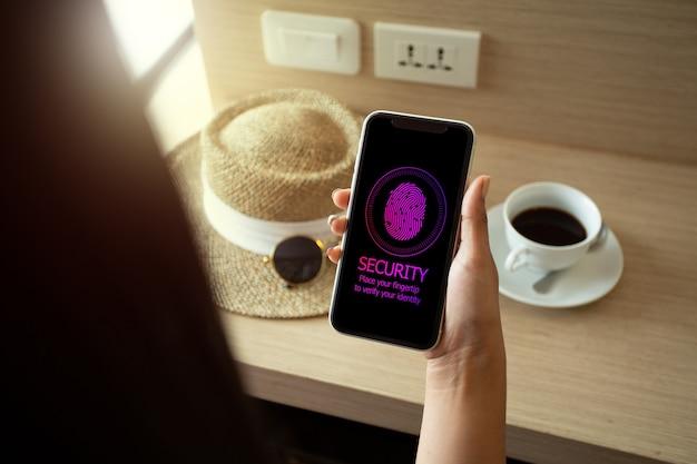 휴가 중인 여성이 스마트폰을 사용하여 fingertip으로 비밀번호에 서명합니다. 모바일 보안 개념입니다.