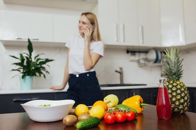 昼食を調理しながら電話で話している台所の女性