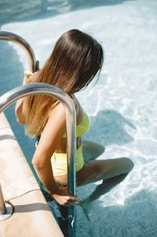 리조트에서 수영장의 사다리에 여자입니다. 그녀는 행복하고 세련되고 원피스로 보입니다.