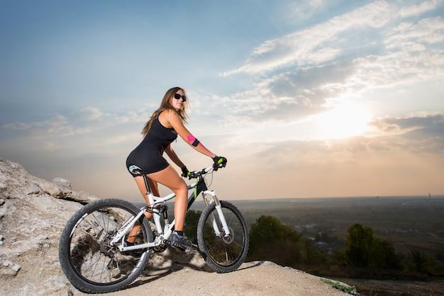 Женщина на горном велосипеде в горах
