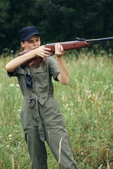 Женщина на природе женщина с оружием целится на охоте за зелеными листьями