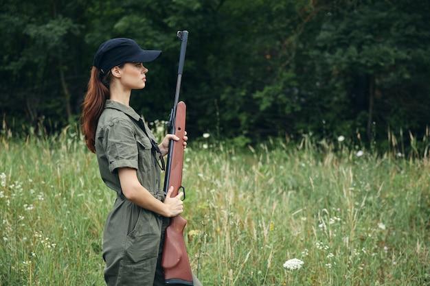 Женщина на природе держит пистолет перед собой черная фуражка, зеленый комбинезон