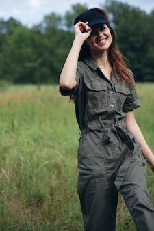 緑のジャンプスーツの休息でフィールドを横切って歩いて笑顔の自然の女性