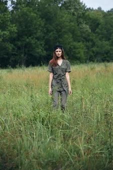背の高い草の緑のジャンプスーツフィールドに立っている自然の女性