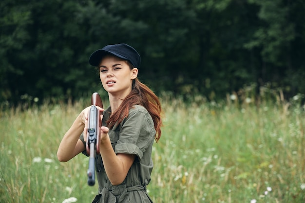 Женщина на природе женщина держит пистолет