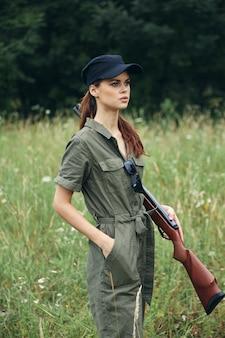 屋外の女性銃を持った女性が黒い帽子のポケットに手をかざす