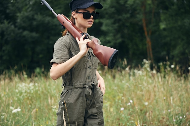 Женщина на открытом воздухе руки на плечах солнцезащитные очки зеленый комбинезон охота