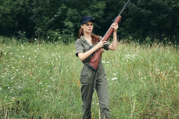 Женщина на открытом воздухе держит пистолет в руках свежий воздух путешествия охота зеленый комбинезон крупным планом