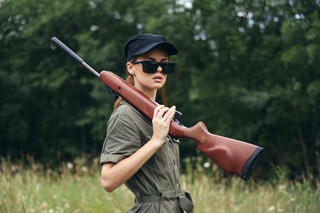 Женщина на открытом воздухе держит оружие на плече, солнцезащитные очки, зеленый комбинезон, зеленый комбинезон, обрезанный вид