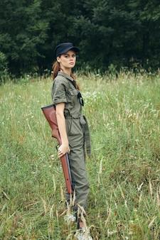 Женщина на открытом воздухе держит оружие в руках природы, охотясь на свежем воздухе, зеленые листья, лесной фон