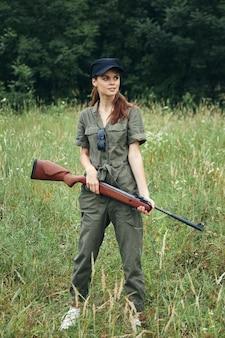 Женщина на открытом воздухе держит оружие в зеленом комбинезоне