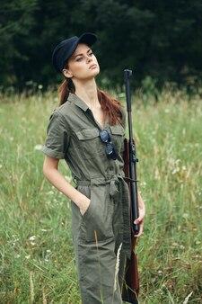 Женщина на открытом воздухе оружие зеленый комбинезон охота образ жизни зеленые листья крупным планом