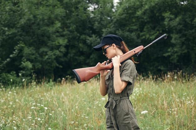 屋外の武器狩猟ライフスタイル旅行グリーンオーバーオールのクローズアップの女性