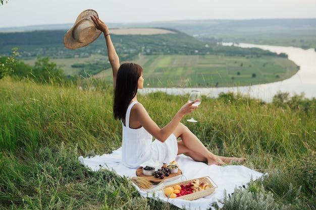 グラスワインと新鮮な果物とピクニックの女性。幸せなライフスタイル。