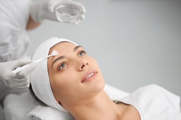 Женщина на процедуре для лица в косметологе