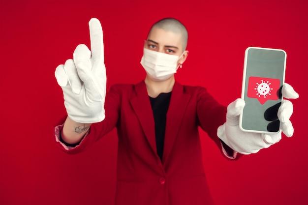 얼굴 마스크를 쓴 빨간색 배경의 여성, 코로나바이러스 삽화가 있는 전화를 보여줍니다. 코로나바이러스 확산, 보호, 예방, 글로벌 전염병 및 전염병의 개념. 격리, 격리.