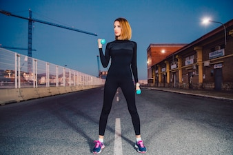 Woman on road exercising with dumbbells
