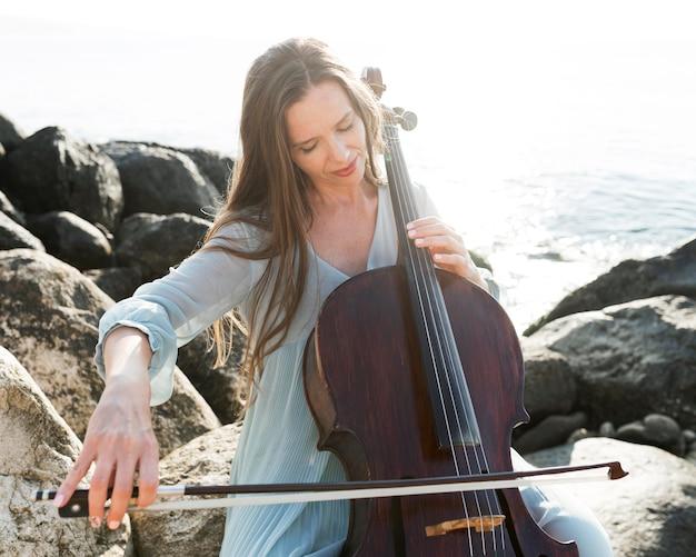 Женщина на скалах играет на виолончели