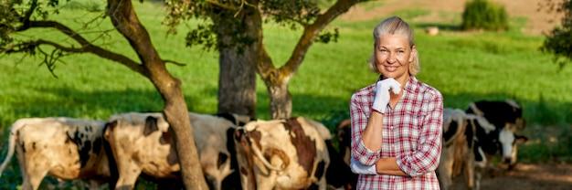 乳牛と田舎の農場の女性。