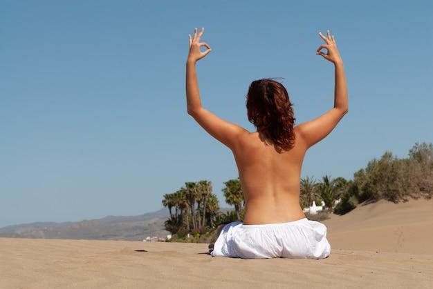 ヨガのポーズと瞑想をしている春または夏の砂丘の上の女性