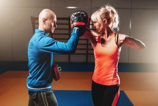 Женщина на тренировке по самообороне с мужским тренером