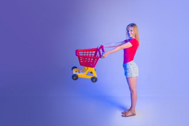 買い物中の女性。スーパーマーケット。買い物。セール。割引。ブラックフライデー。購入。買い物中の女性。買いまくる。空のショッピングカートを持つ女性。テキスト用のスペースをコピーします。