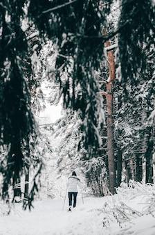 Женщина на лыжах в лесу среди заснеженных веток в теплой одежде