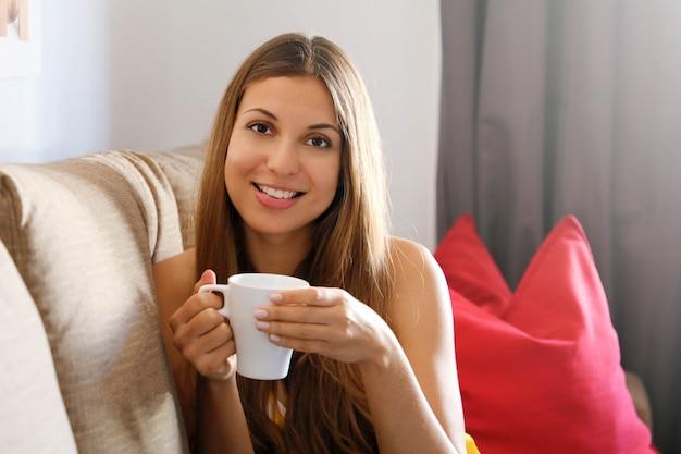 コーヒーのマグカップを保持しているソファの上の女性