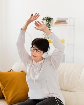 ソファでヘッドフォンで音楽を聴く女性