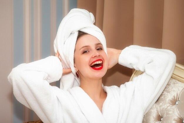 Женщина на софе гостиничного номера после душа. симпатичная женщина славянской внешности в халате и полотенце на голове