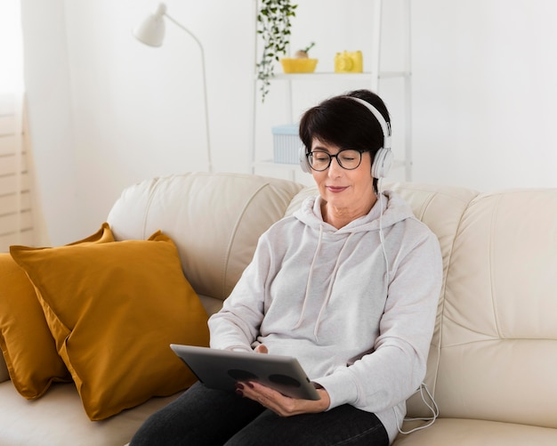 タブレットとヘッドフォンが付いているソファーの女性