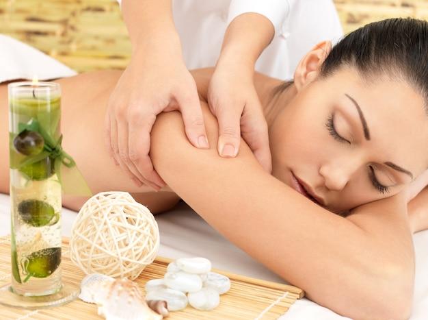 ビューティーサロンで体のスパマッサージをしている女性。