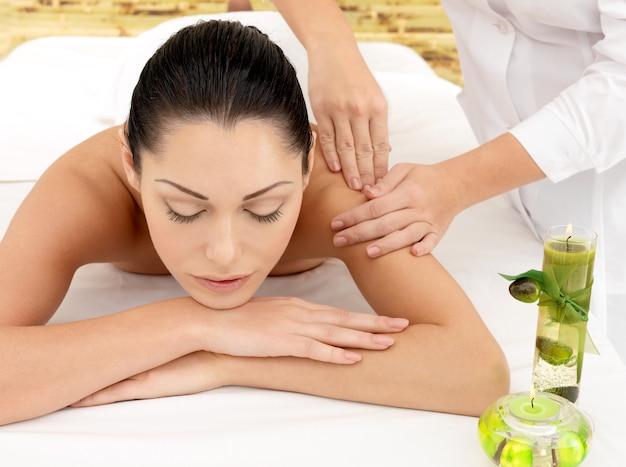 ビューティーサロンで肩のスパマッサージをしている女性。