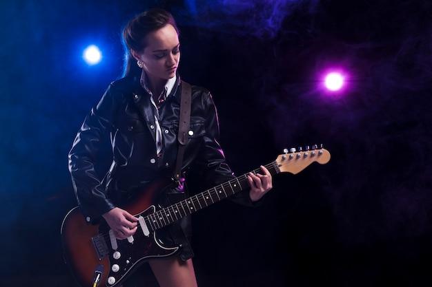ギターとストラップを持つステージ上の女性
