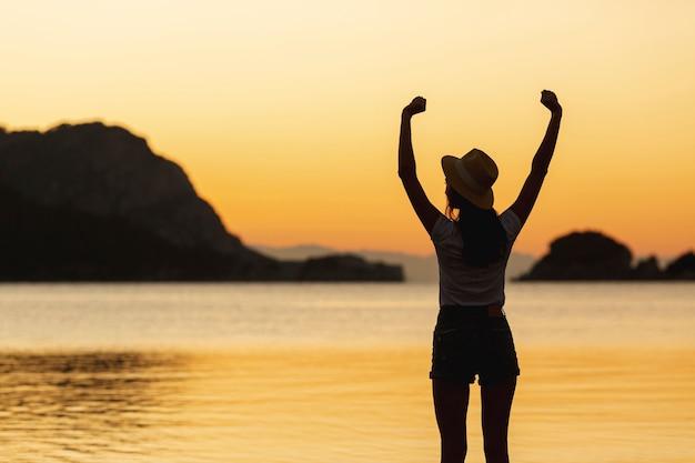 湖の岸に夕日の女性