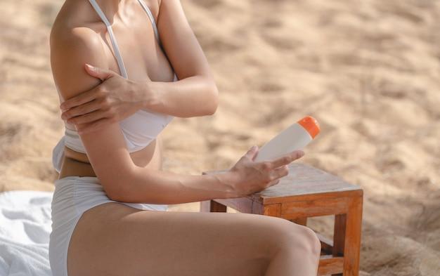 Женщина на пляже, применяя солнцезащитный крем, сидя на полотенце.
