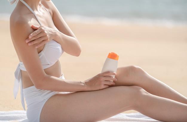 タオルの上に座っている間日焼け止めを適用するビーチの女性。