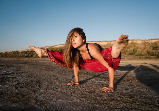 ヨガのアーサナをやって日没時にビーチで女性。朝の自然ストレッチウォームアップトレーニング