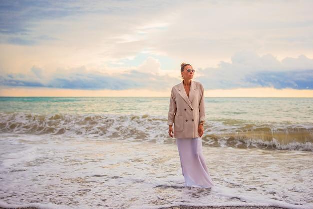Женщина на пляже, наслаждаясь летними каникулами