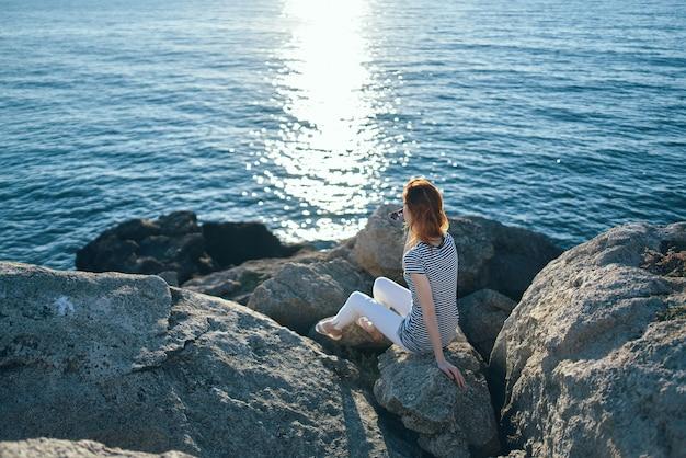 大きな石の山のビーチで女性日没夏の上面図