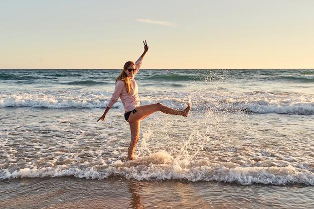 彼女の足で水をはねかける浜辺の女