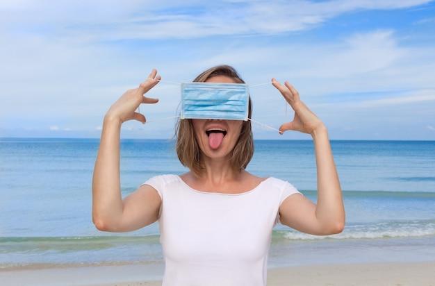 医療マスクが付いている浜の女性。
