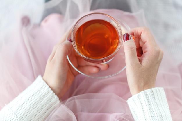 お茶を一杯のベッドの上の女性