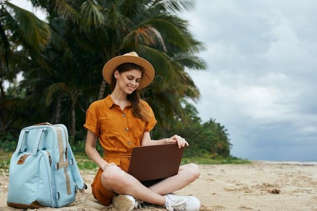 島の女性は、ラップトップのリモートワークの前に砂の上に座っています