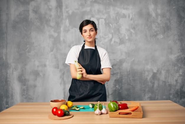 野菜まな板を切る台所の女性