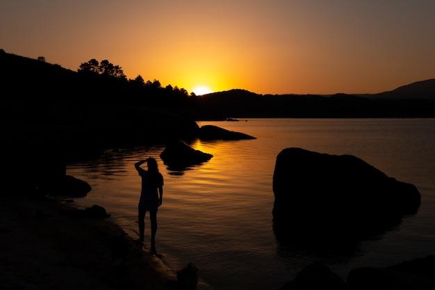 日没時の湖のほとりの女性人生の困難を克服するコピースペース自信