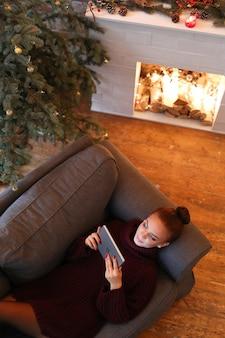 タブレットが付いているソファーの女性