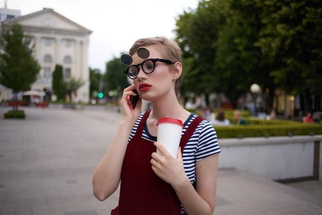 음료 패션으로 안경 유리를 쓰고 전화 통화를 하는 거리의 여자
