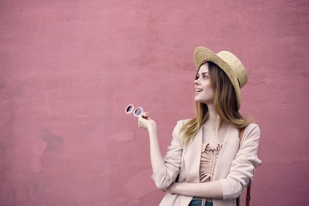 Женщина на улице в шляпе и очках розовая настенная модель